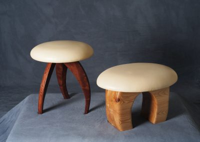 Stool on left is made with bubinga with a leather seat Stool on right is made with white cedar with a leather seat
